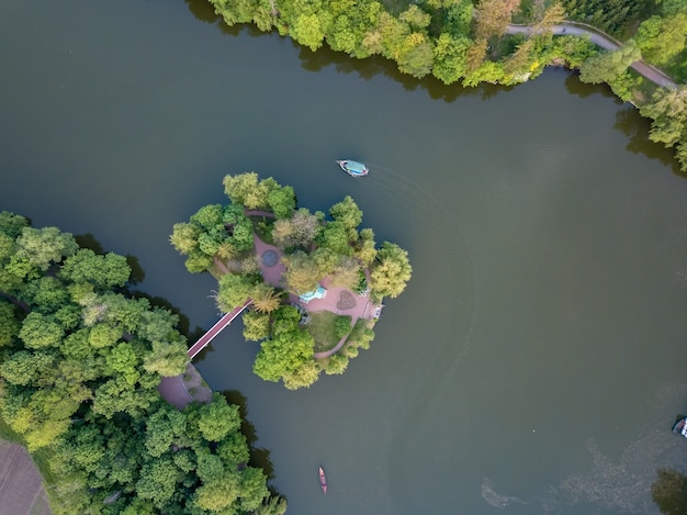 Aerial view of a small lake in the middle of a forest and an island with a bridge among a huge green forest. a small boat is going along the water. photo by drone