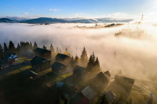 Aerial view of a small village houses on hill top in fall foggy mountains at sunrise.