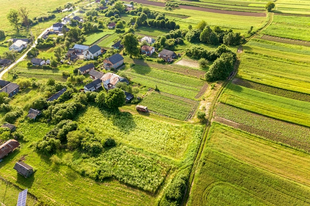 Aerial view of a small village win many houses and green agricultural fields in spring with fresh vegetation after seeding season on a warm sunny day.