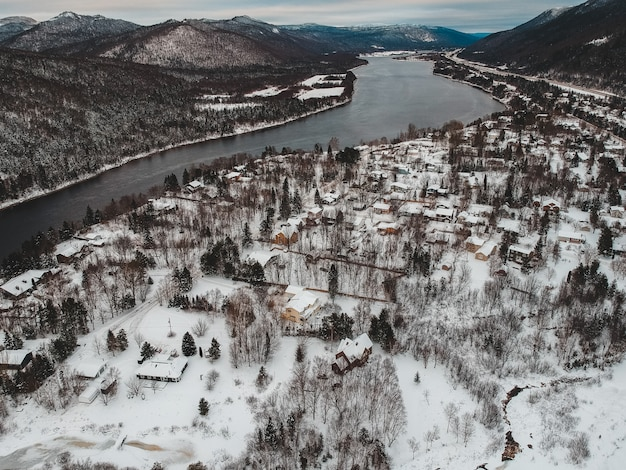 Aerial view of snow covered houses beside body of water