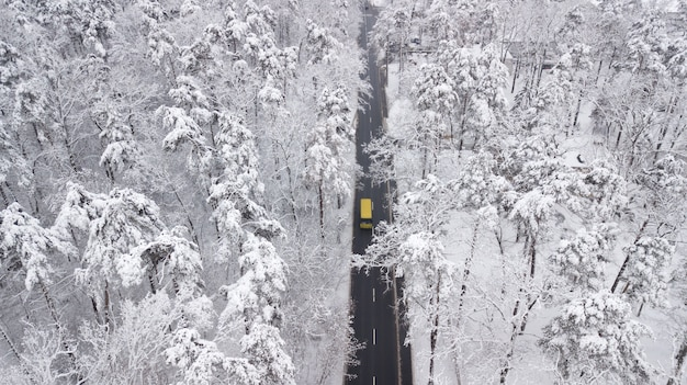 Aerial view of snow covered road in winter forest, truck