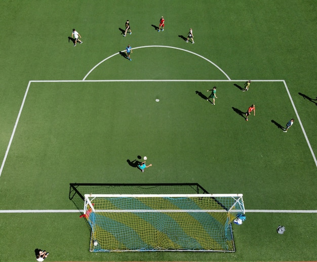 Aerial view of soccer players on a sports field playing a game of football