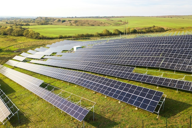 Aerial view of solar power plant under construction on green field assembling of electric panels for producing clean ecologic energy