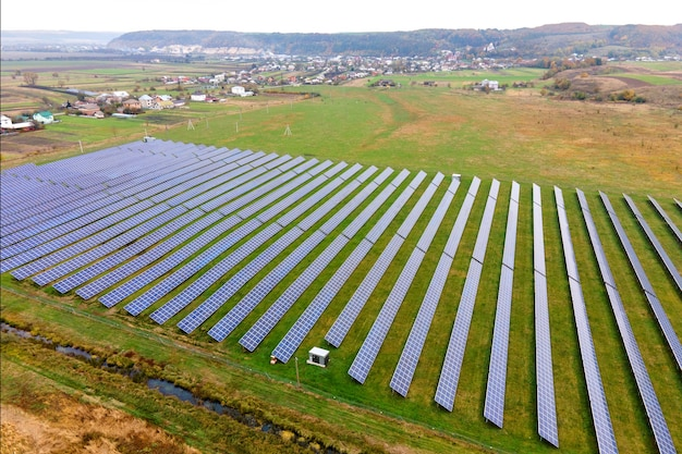 Aerial view of solar power plant on green field. electric farm with panels for producing clean ecologic energy.