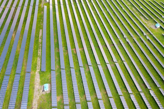 Aerial view of solar power plant on green field electric panels for producing clean ecologic energy