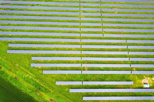 Aerial view of solar power plant on green field. electric panels for producing clean ecologic energy.