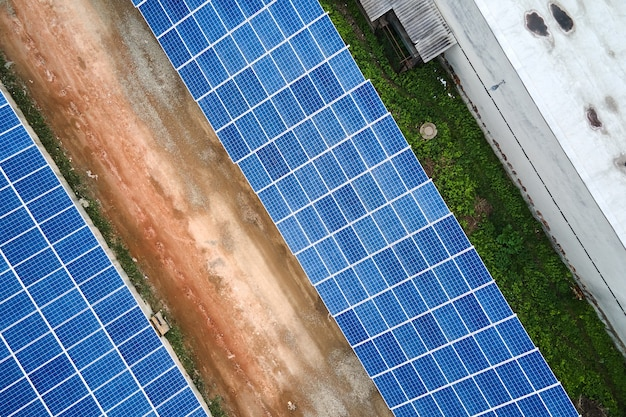 Aerial view of solar power plant with blue photovoltaic panels mounted on industrial building roof for producing green ecological electricity. production of sustainable energy concept.