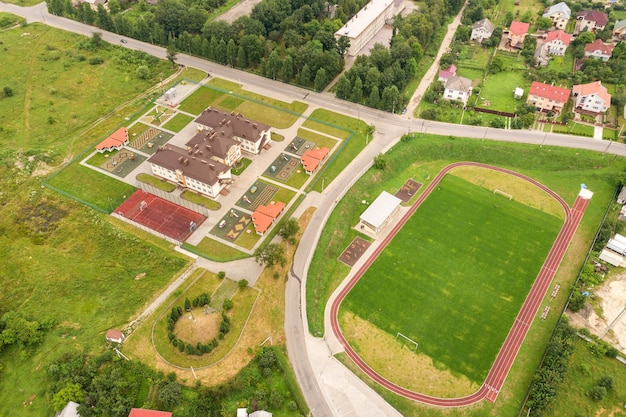 Aerial view of sports stadium with red running tracks and green grass football field near school building in rural area.