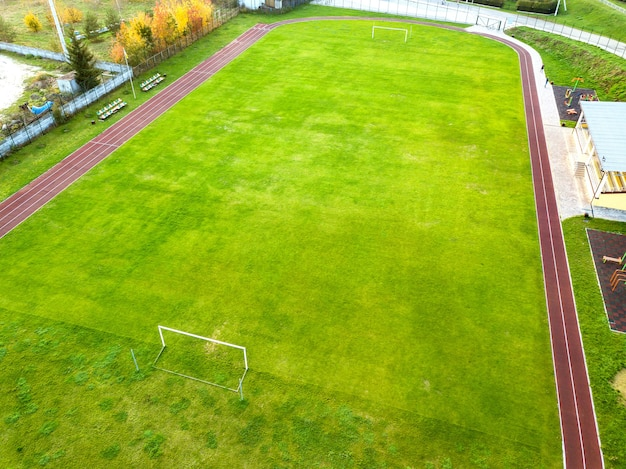 Aerial view of sports stadium with red running tracks and green grass football field.