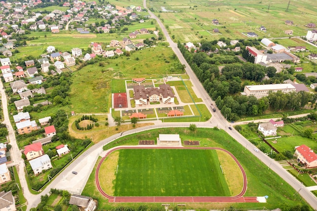 Aerial view of sports stadium with red running tracks and green grass football field