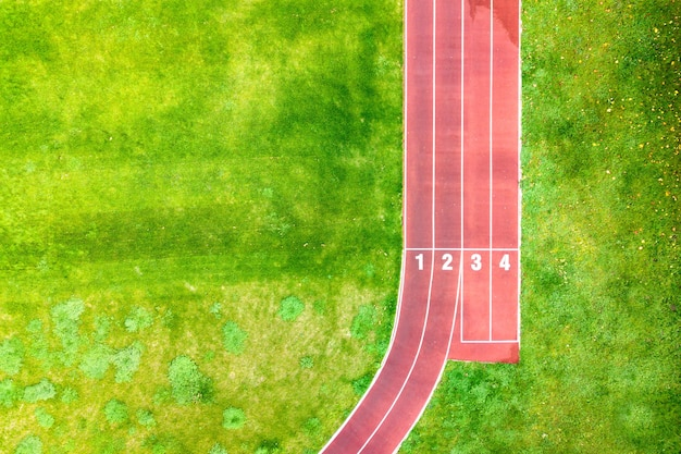 Aerial view of sports stadium with red running tracks with numbers