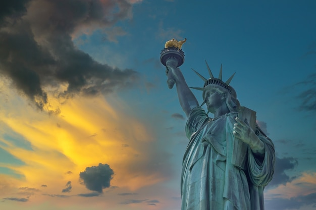 Aerial view of the statue of liberty at sunset in manhattan island new york city, united states
