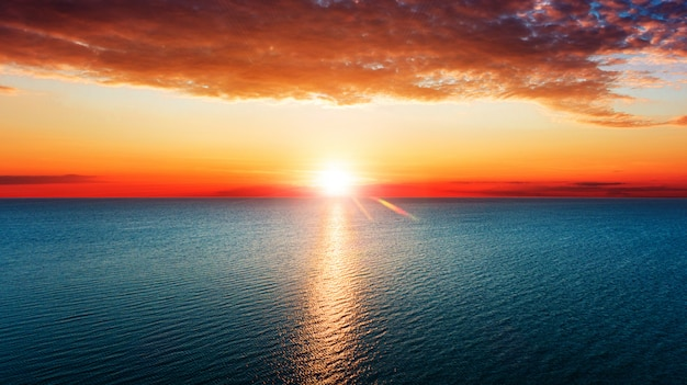 Aerial view of sun rising over sea.