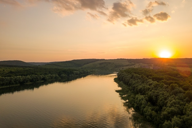 Aerial view of sunset over wide dnister river and distant rocky hills in bakota area, part of the national park