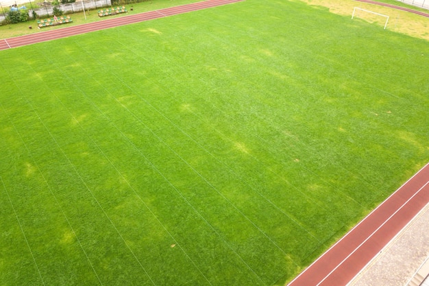 Aerial view of surface of green freshly cut grass on football stadium field with red running tracks in summer.