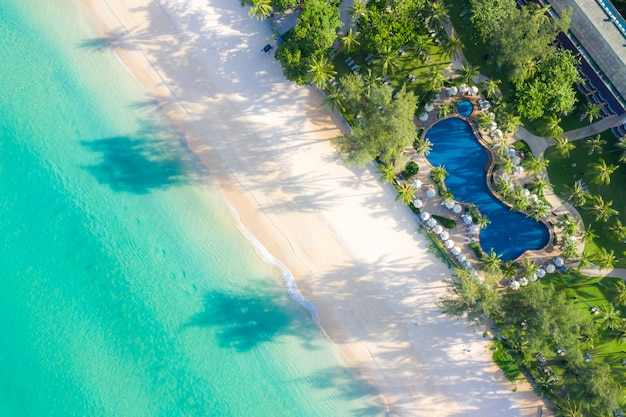 Aerial view of swimming pool with sea and beach in luxury hotel and resort for travel and vacation