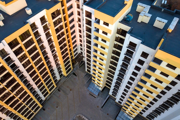 Aerial view of tall apartment building complex. blue flat roof with chimneys, inner yard, row of windows. drone photography.