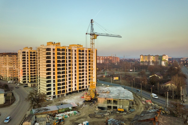 Aerial view of tall apartment building complex, unfinished building with scaffolding and tower crane on blue sky copy space. drone photography.