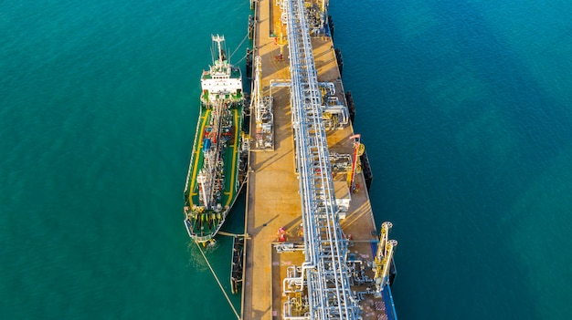 Aerial view tanker ship unloading at port, business import export oil with tanker ship transportation oil from refinery on the sea.