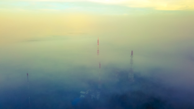 Aerial view of telecom tower on top of mountain with misty.