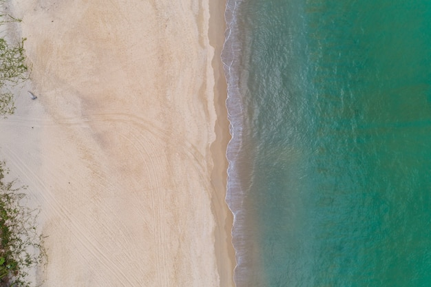 Aerial view top down of beautiful tropical beach aerial drone shot of turquoise sea water surface at the beach space for text and summer background.
