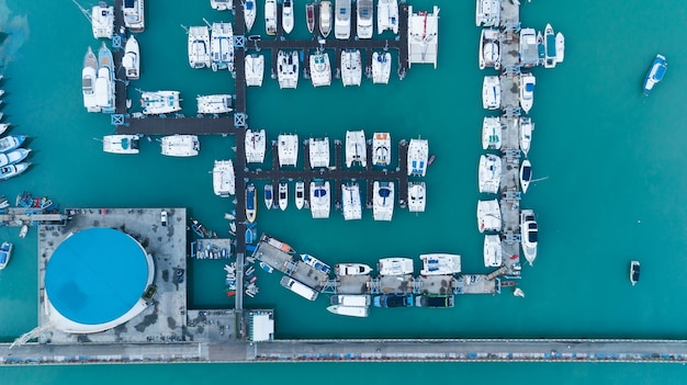 Aerial view top down drone shot of yacht and sailboat parking in marina transportation and travel background concept.