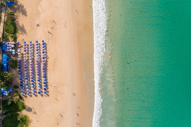 Aerial view top down flying above turquoise ocean and waves washing sandy beach