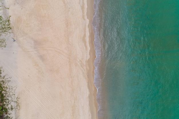 上から見た美しい熱帯のビーチの上から見たテキストと夏の背景のビーチスペースでターコイズブルーの海の水面の空中ドローンショット。