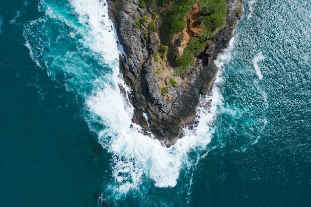 Aerial view top down seashore big wave crashing on rock cliff beautiful dark sea surface in sunny day summer background amazing seascape top view seacoast at phuket thailand.
