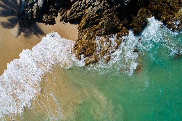 공중 보기 바위 돌 해변에 충돌 하는 해변 파도 하향식 화창한 날에 아름 다운 청록색 바다 표면 좋은 날씨 하루 여름 배경입니다.