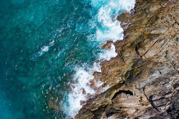 공중 보기 해변에 충돌 하는 해변 파도를 하향식 화창한 날에 아름 다운 청록색 바다 표면 좋은 날씨 날 여름 배경 놀라운 바다 상위 뷰입니다.