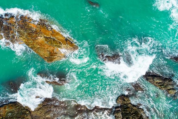 공중 보기 해변에 충돌 하는 해변 파도 하향식 화창한 날에 아름 다운 청록색 바다 표면 좋은 날씨 하루 여름 배경입니다.