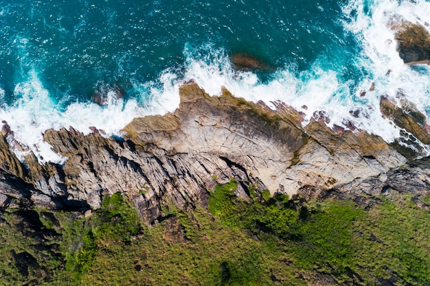 Aerial view top down seashore wave crashing on seashore beautiful turquoise sea surface in sunny day good weather day summer background amazing seascape top view.
