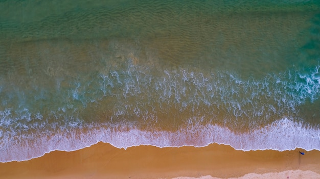 Aerial view top view amazing nature background of sea beach wave crashing on sandy shore and clear water of phuket thailand ocean at sunset or sunrise time.