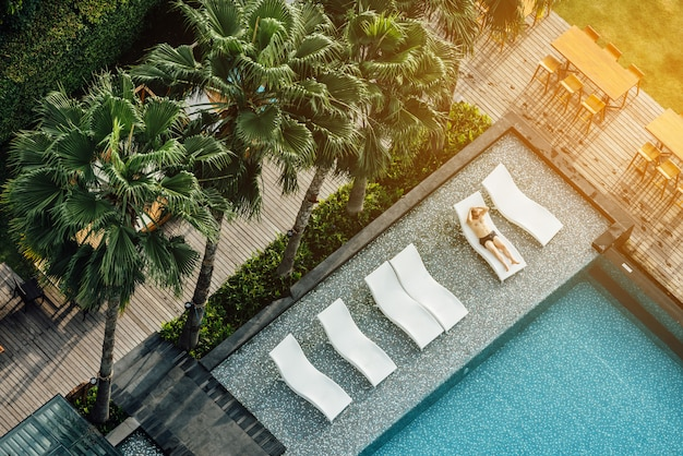 Aerial view of tourist lay down on outdoor chairs near swimming pool with palm trees in hotel area.