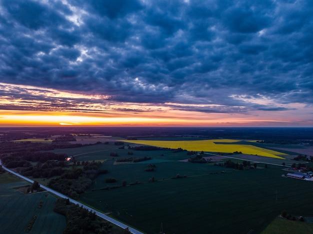 遠くに黄色い菜の花畑と夕日に向かって空撮