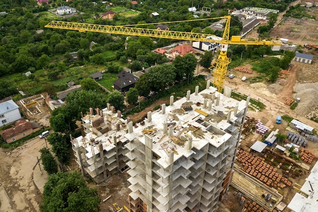 Aerial view of tower lifting crane and concrete frame of tall apartment residential buildings under construction in a city.