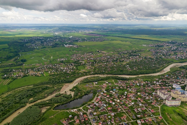 Aerial view of town or village with rows of buildings and curvy streets between green fields in summer. countryside landscape from above.