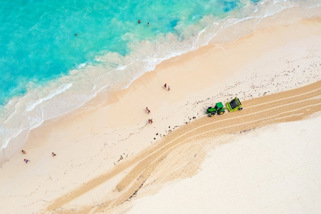 Aerial view of tractor cleaning the beach from seaweed