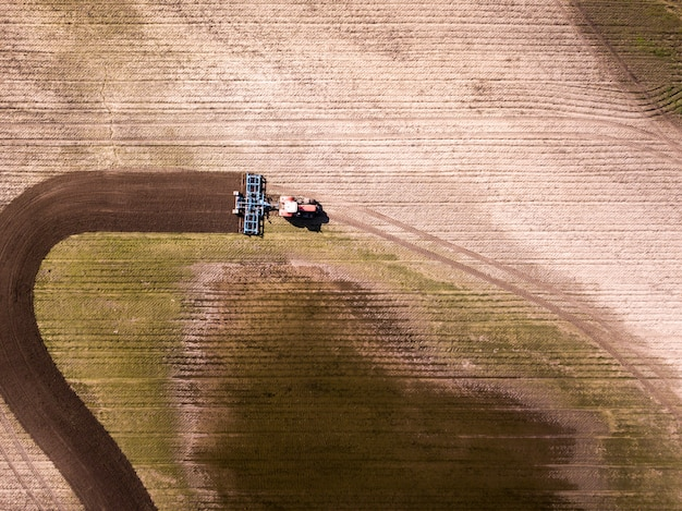 Aerial view of the tractor in the field, agricultural field work. tractor cultivating field, aerial view