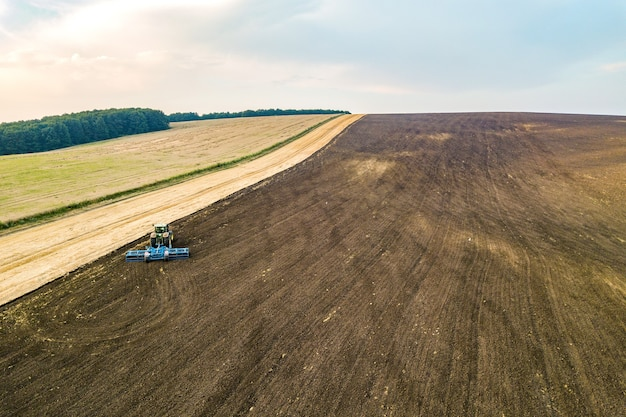 Aerial view of a tractor plowing agriculture farm field after harvesting in late autumn