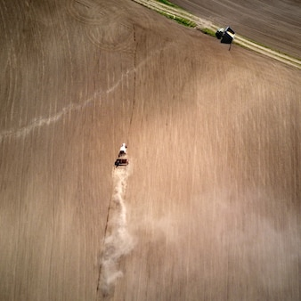 Aerial view of the tractor plowing spring field, a column of dust stretches behind the tractor, ukraine. photo from the drone