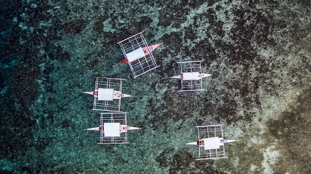 Aerial view traditional philippines boats on coral reef