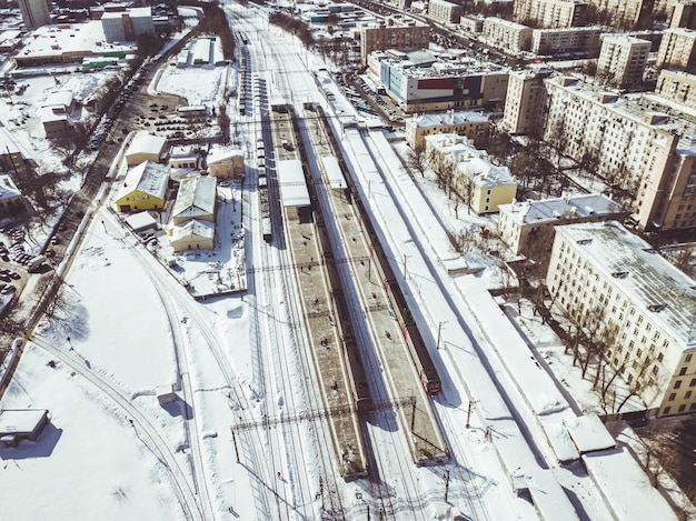 Aerial view of train on railway passing by in the city on a winter day