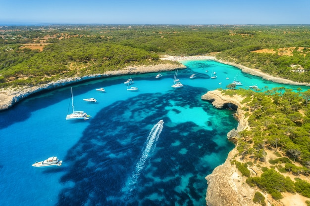 Aerial view of transparent sea with blue water, sandy beach, rocks, green trees, yachts and boats in sunny morning in summer