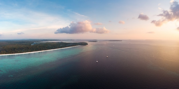 Aerial view tropical beach island reef caribbean sea at sunset.