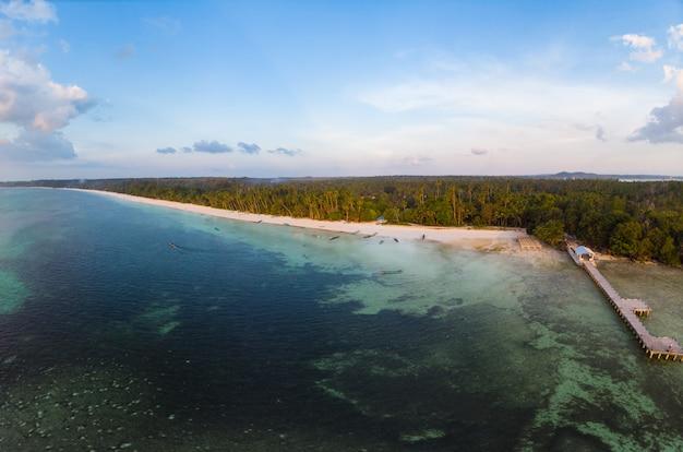 Aerial view tropical beach island reef caribbean sea at sunset.