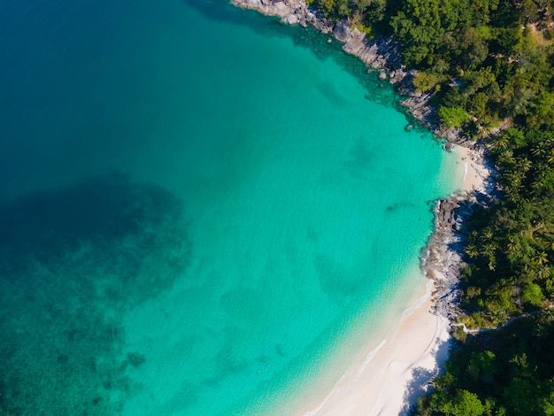 Aerial view of turquoise beach with white sand and jungle