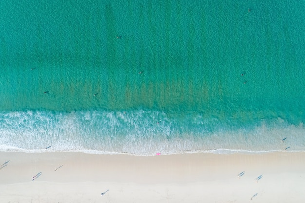 Aerial view of the turquoise color of ocean surface with waves washing on the coast of the andaman ocean amazing top down nature landscape seascape view beautiful for travel background and website.