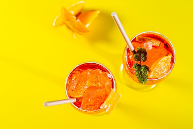Aerial view of two glasses of the italian aperol spritz cocktail with mint